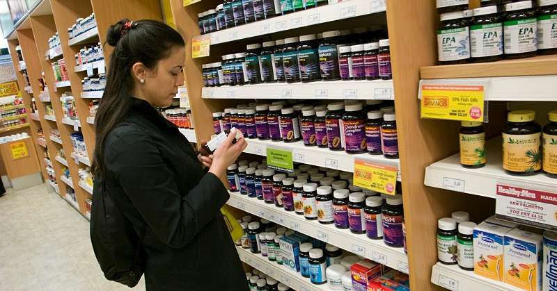 girl looking at products in a health supplement aisle