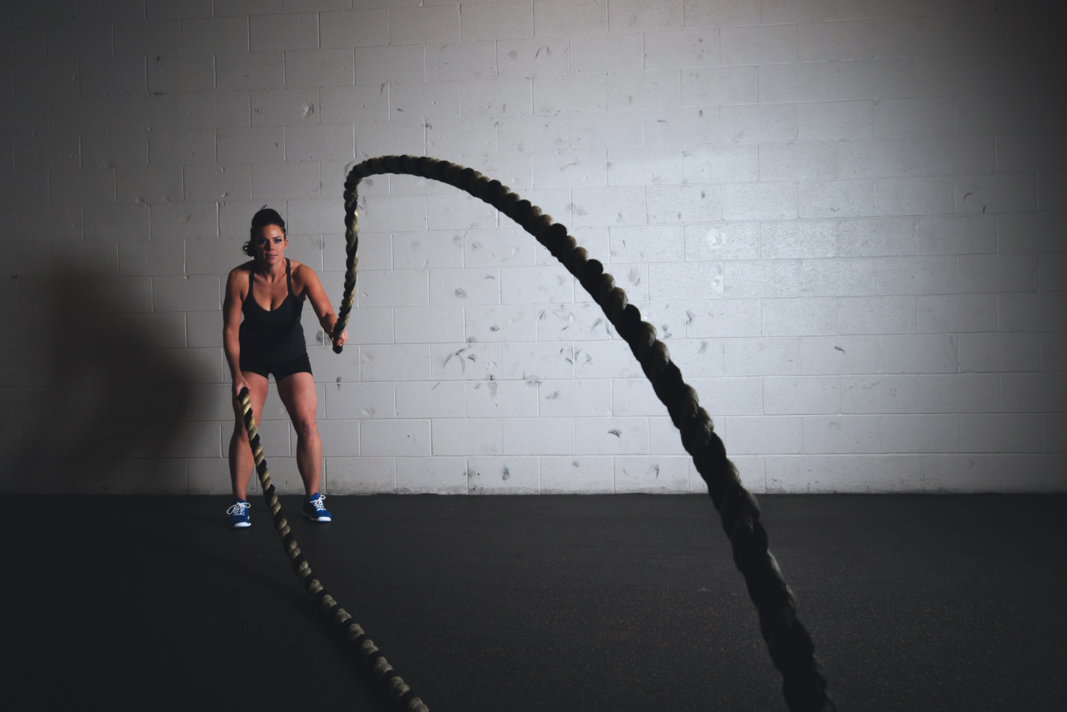 Woman in black using battling ropes at the gym