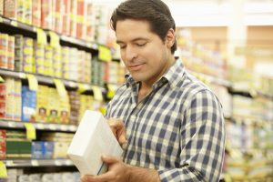 Man reading a nutrition label in a grocery store