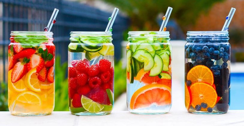 four jars of fresh fruit infused water