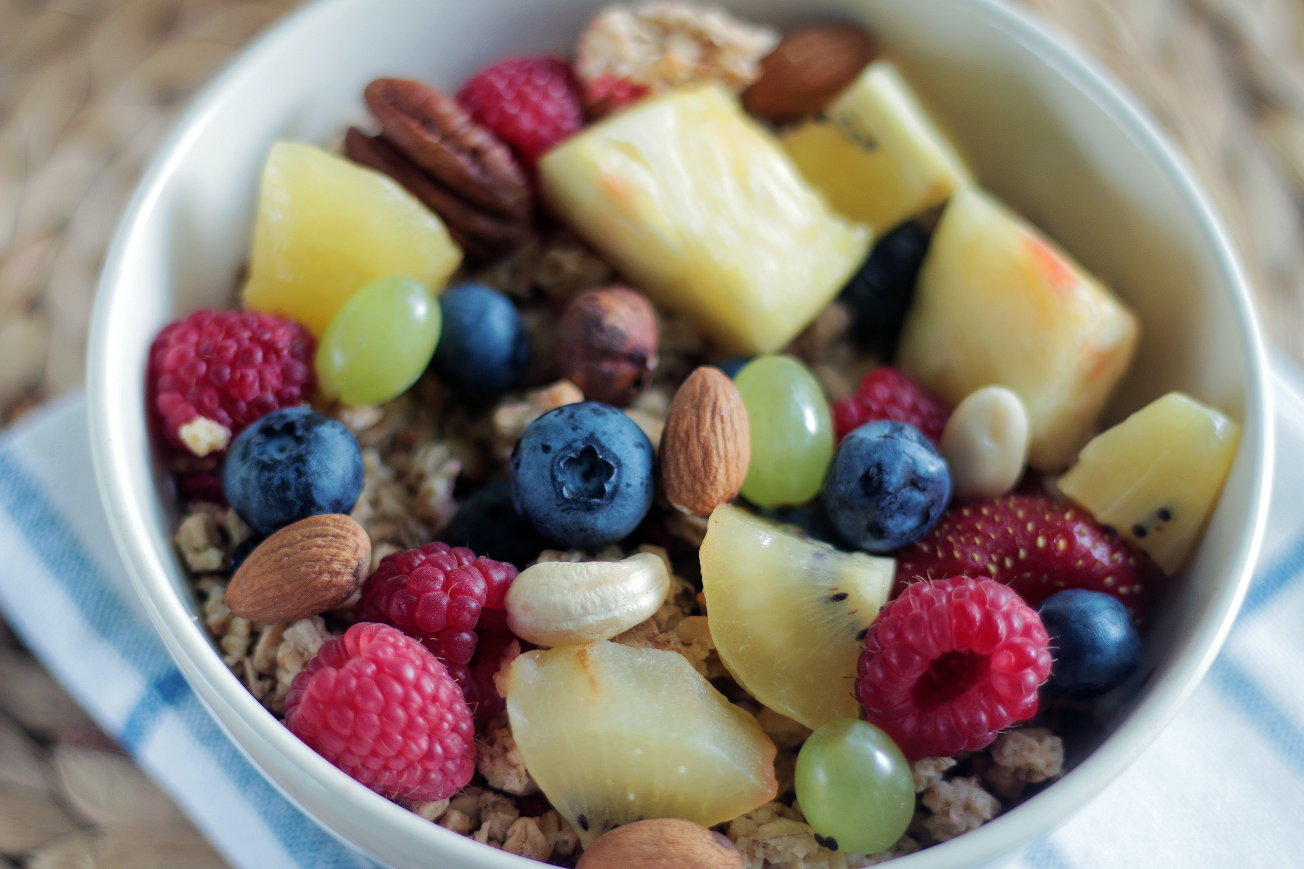 granola, almonds, and fresh fruit in a white bowl