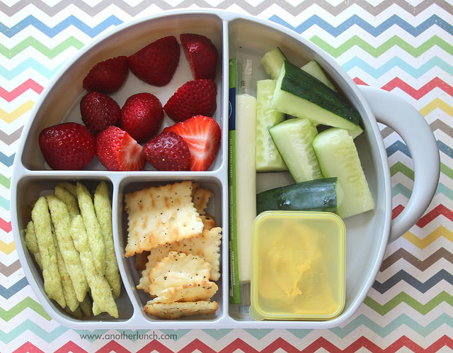healthy snack box with cucumber, cheese stick, hummus, crackers, and strawberries