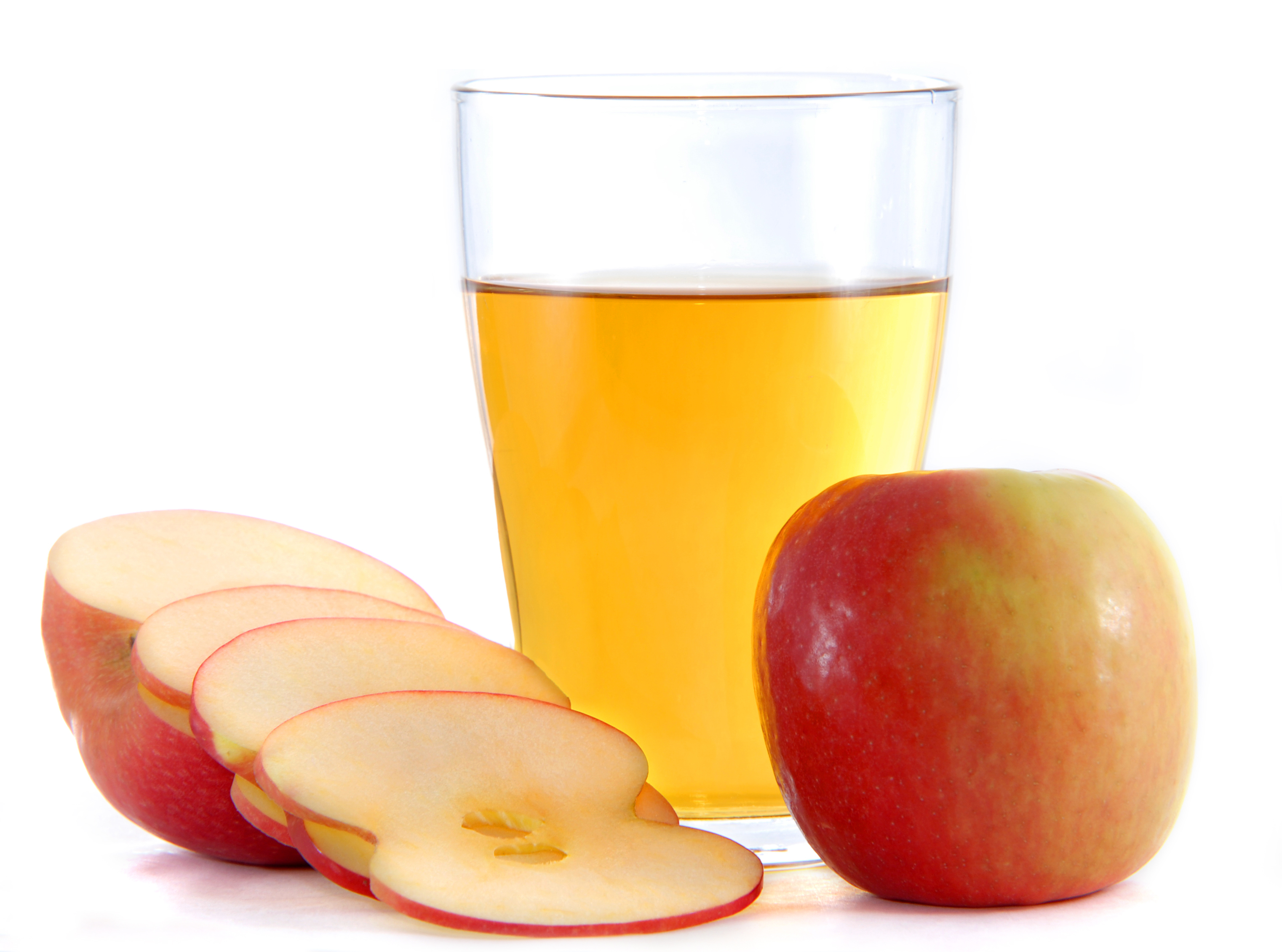 apple cider vinegar in a glass next to an apple and apple slices